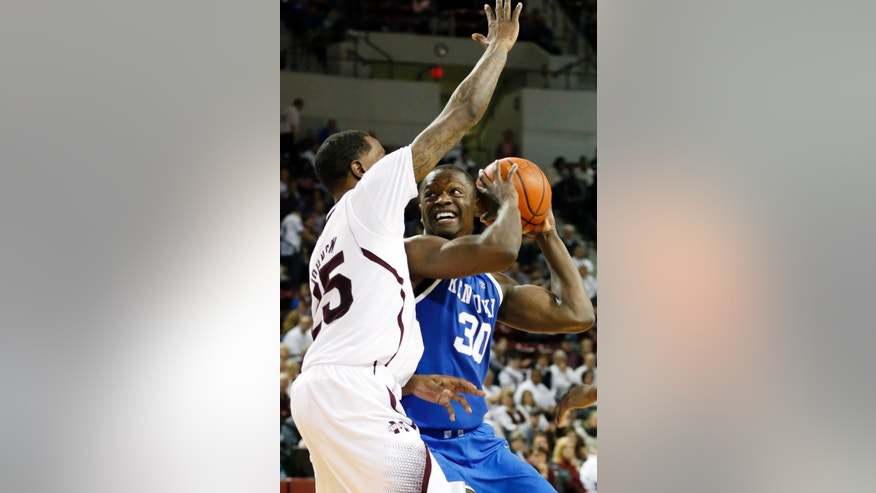 Kentucky forward Julius Randle (30) tries to get past the defense of Mississippi State forward Roquez Johnson (25) during the second half of an NCAA college basketball game in Starkville, Miss., Saturday, Feb. 8, 2014. Kentucky won 69-59. (AP Photo/Rogelio V. Solis)