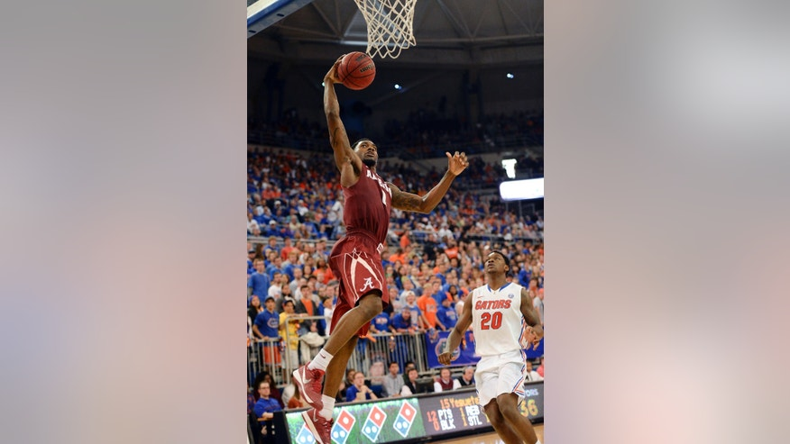 Alabama's Algie Key goes to the basket for two points with Florida guard Michael Frazier II (20) unable to stop the shot during the second half of an NCAA college basketball game Saturday, Feb. 8, 2014 in Gainesville, Fla. Florida won 78-69.(AP Photo/Phil Sandlin)