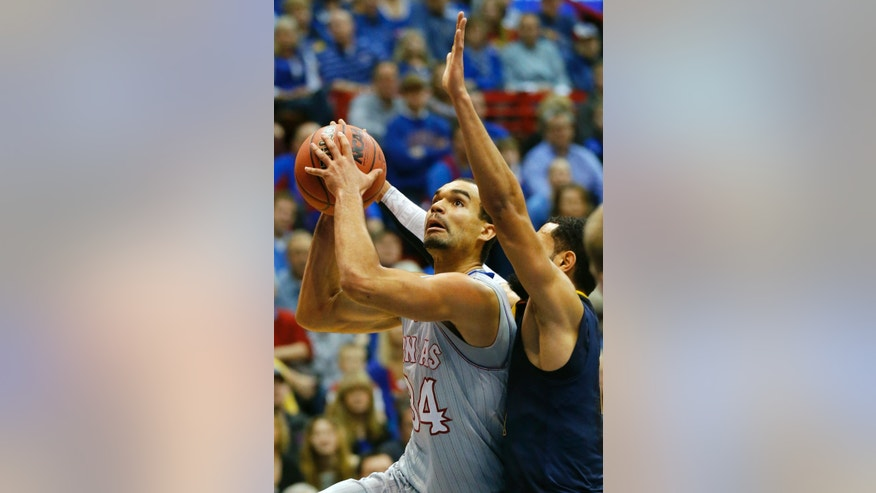 Kansas forward Perry Ellis (34) shoots while covered by West Virginia forward Remi Dibo, right, during the first half of an NCAA college basketball game in Lawrence, Kan., Saturday, Feb. 8, 2014. (AP Photo/Orlin Wagner)