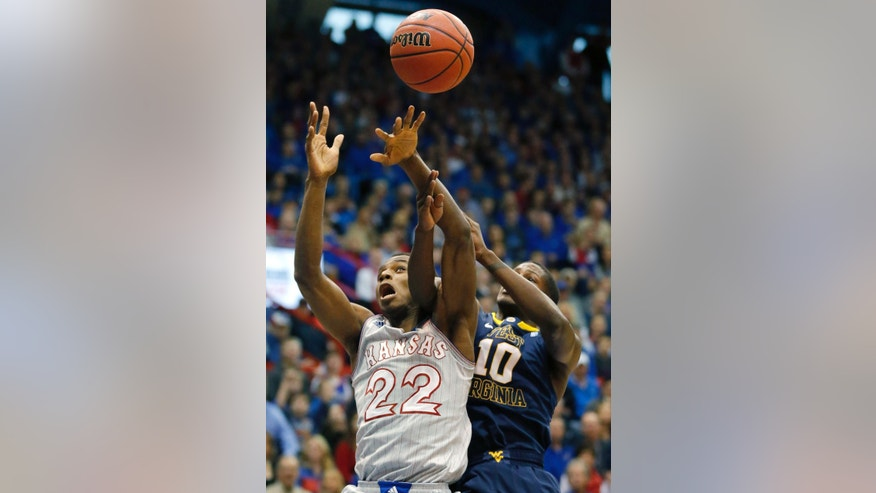 Kansas guard Andrew Wiggins (22) rebounds against West Virginia guard Eron Harris (10) during the first half of an NCAA college basketball game in Lawrence, Kan., Saturday, Feb. 8, 2014. (AP Photo/Orlin Wagner)