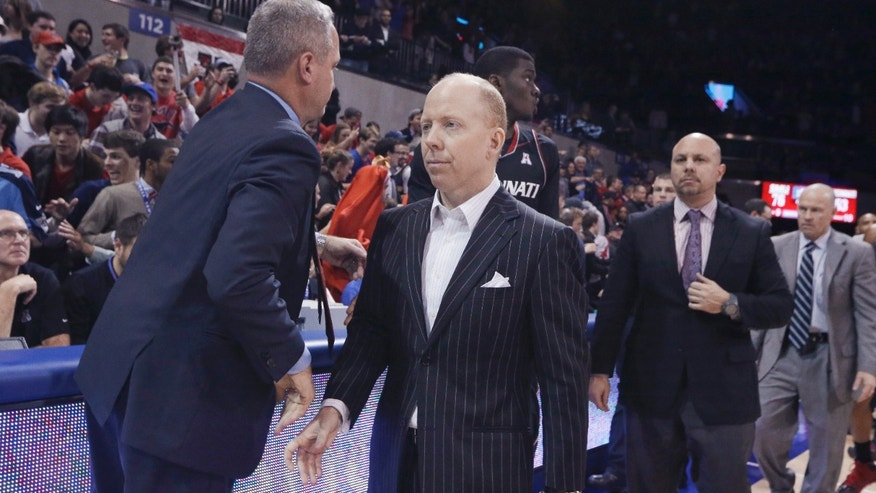 Cincinnati coach Mick Cronin, center, walks off the court after an NCAA college basketball game against SMU on Saturday, Feb. 8, 2014, in Dallas. SMU won 76-55. (AP Photo/LM Otero)