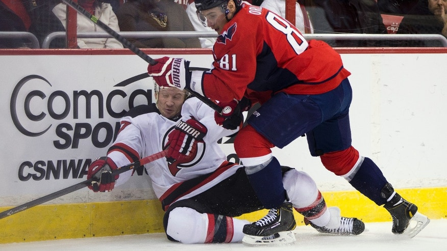 Washington Capitals defenseman Dmitry Orlov, right, hits New Jersey Devils right wing Michael Ryder during the first period of an NHL hockey game on Saturday, Feb. 8, 2014, in Washington. (AP Photo/ Evan Vucci)