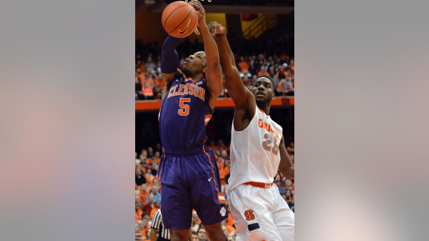 Clemson's Jaron Blossomgame is fouled by Syracuse's Rakeem Christmas, right, during the first half of an NCAA college basketball game in Syracuse, N.Y., Sunday, Feb. 9, 2014. (AP Photo/Kevin Rivoli)