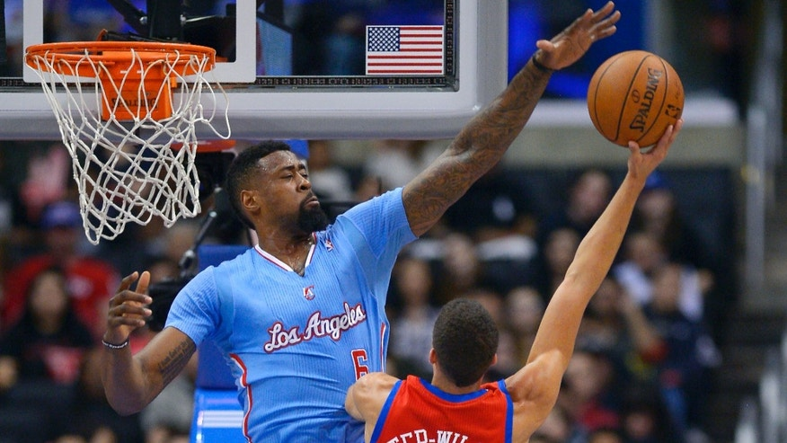 Los Angeles Clippers center DeAndre Jordan, left, rejects a shot by Philadelphia 76ers guard Michael Carter-Williams during the first half of an NBA basketball game Sunday, Feb. 9, 2014, in Los Angeles. (AP Photo/Mark J. Terrill)