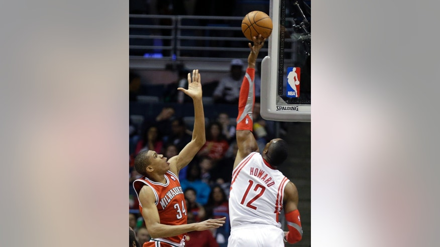 Houston Rockets' Dwight Howard, right, blocks a shot by Milwaukee Bucks' Giannis Antetokounmpo (34) during the first half of an NBA basketball game Saturday, Feb. 8, 2014, in Milwaukee. (AP Photo/Jeffrey Phelps)