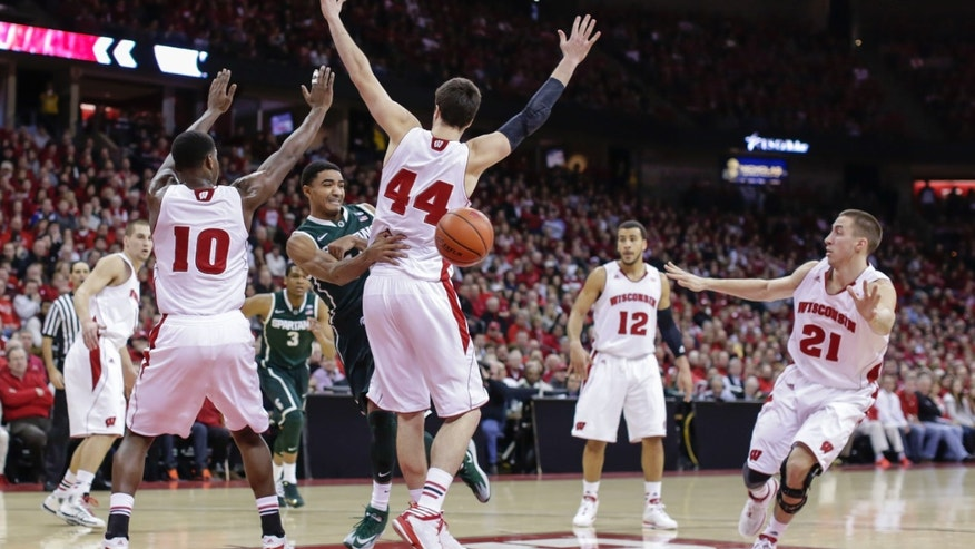Michigan State's Gary Harris, second from front left, passes between Wisconsin's Nigel Hayes (10) and Frank Kaminsky (44) during the first half of an NCAA college basketball game on Sunday, Feb. 9, 2014, in Madison, Wis. (AP Photo/Andy Manis)