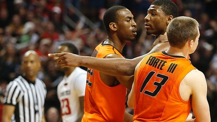 Feb. 8, 2014: Oklahoma State's Markel Brown (22) and Phil Forte (13) hold Marcus Smart (33) after Smart shoved a fan during their NCAA college basketball game in Lubbock, Texas.