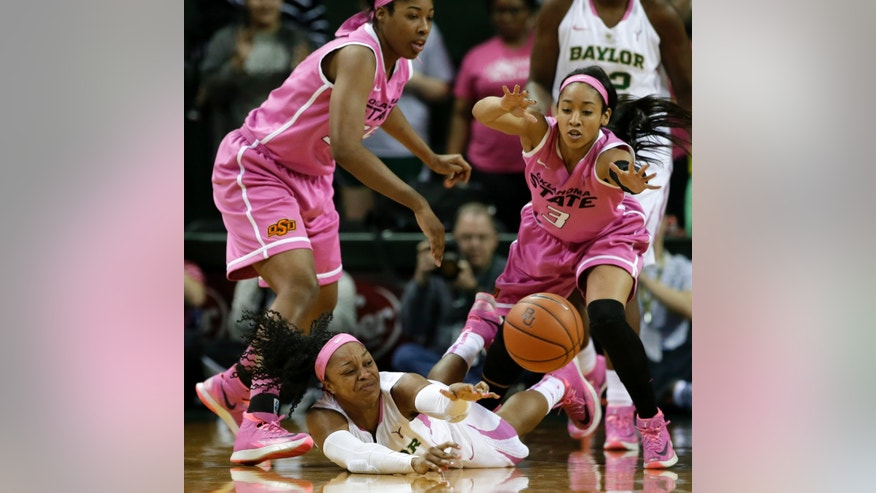 Baylor Bears' Odyssey Sims (0) passes the ball after winning control of it on a scramble on the floor against Oklahoma State 's LaShawn Jones, left, and Tiffany Bias (3) in the first half of an NCAA college basketball game on Sunday, Feb. 9, 2014, in Waco, Texas. (AP Photo/Tony Gutierrez)