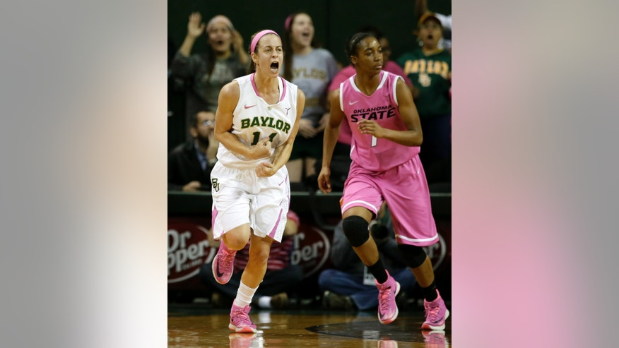 Baylor's Makenzie Robertson (14) celebrates after scoring a 3-point basket in front of Oklahoma State's Brittany Atkins (1) in the first half of an NCAA college basketball game on Sunday, Feb. 9, 2014, in Waco, Texas. Both teams wore uniforms accented with pink for breast cancer awareness. (AP Photo/Tony Gutierrez)