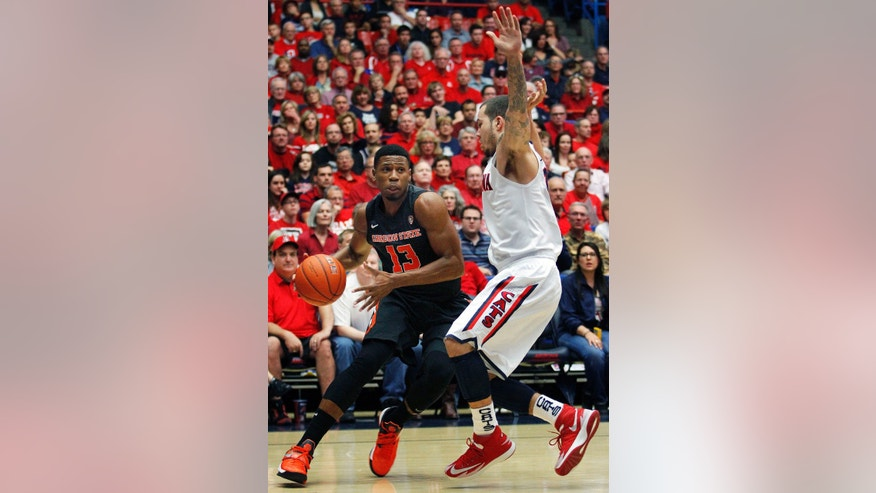 Oregon State's Langston Morris-Walker (13) dribbles around the defense of Arizona's Gabe York, right, in the first half of an NCAA college basketball game on Sunday, Feb. 9, 2014, in Tucson, Ariz. (AP Photo/John MIller)
