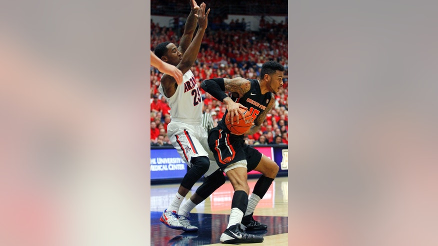 Oregon State's Eric Moreland (15) looks to pass against the defense of Arizona's Rondae Hollis-Jefferson (23) in the first half of an NCAA college basketball game on Sunday, Feb. 9, 2014, in Tucson, Ariz. (AP Photo/John MIller)