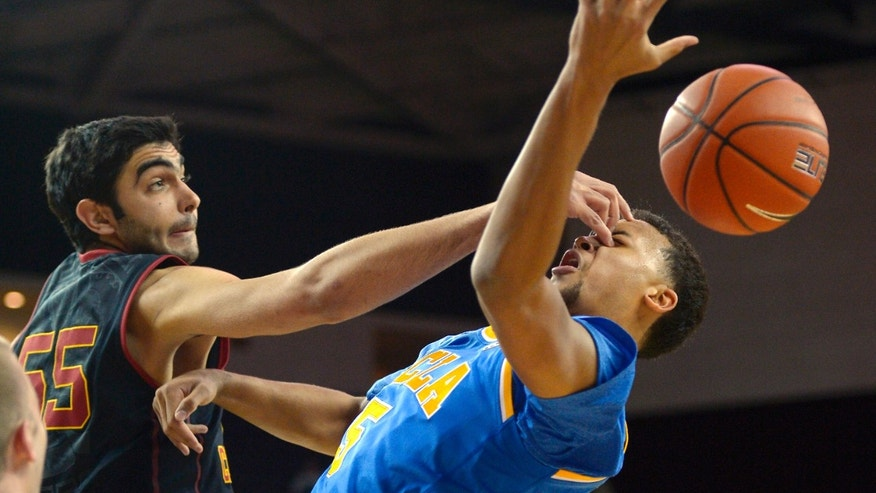 Southern California center Omar Oraby, left, pokes UCLA guard Kyle Anderson in the face after blocking his shot during the first half of an NCAA college basketball game, Saturday, Feb. 8, 2014, in Los Angeles. (AP Photo/Mark J. Terrill)