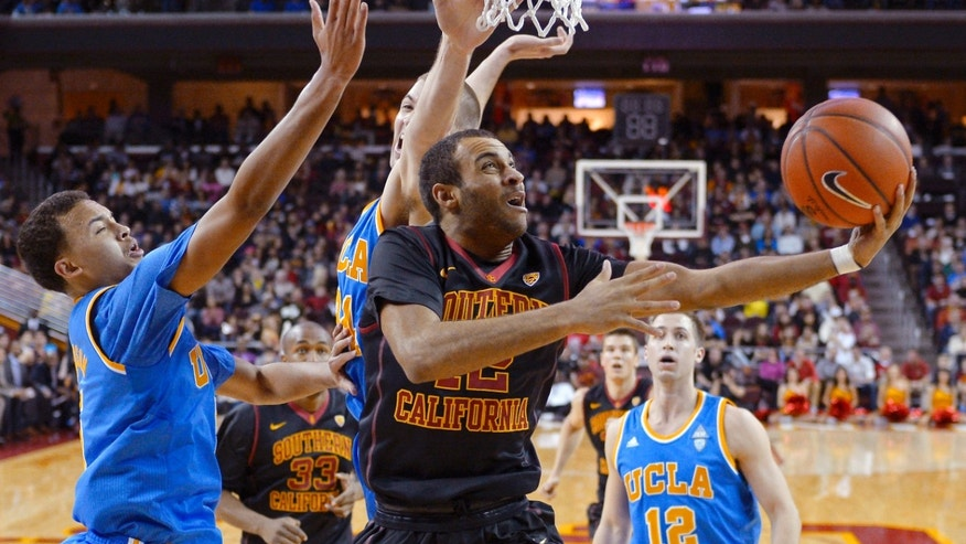 Southern California guard Julian Jacobs, right, shoots as UCLA guard Kyle Anderson, left, and forward Travis Wear defend during the first half of an NCAA college basketball game, Saturday, Feb. 8, 2014, in Los Angeles. (AP Photo/Mark J. Terrill)
