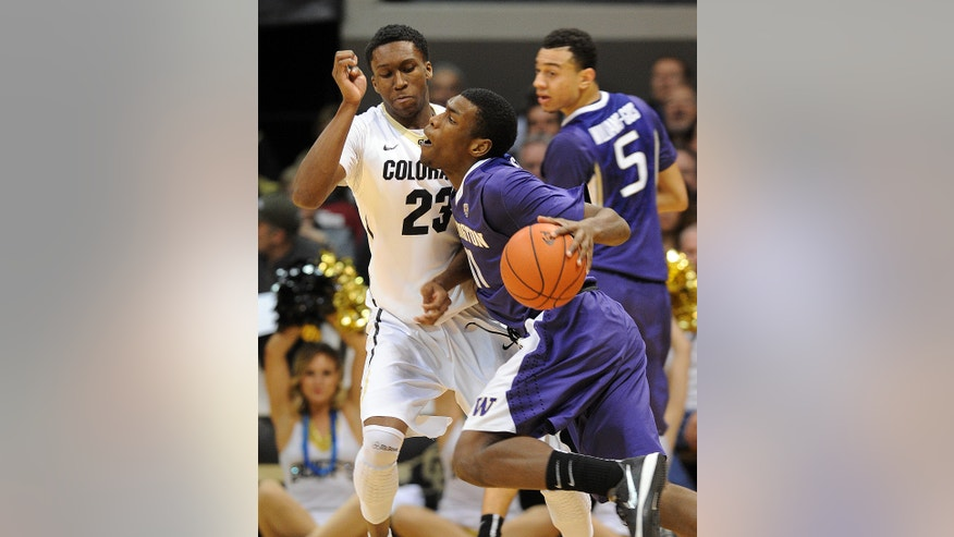 Mike Anderson, right, of Washington, runs into Jaron Hopkins of Colorado during the first half of an NCAA college basketball game in Boulder, Colo., Sunday, Feb. 9, 2014. (AP Photo/Daily Camera, Cliff Grassmick)