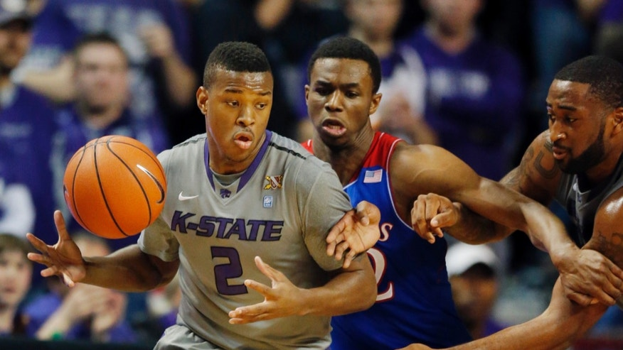 Kansas State guard Marcus Foster (2) tries to go around Kansas guard Andrew Wiggins, center, during the first half of an NCAA college basketball game in Manhattan, Kan., Monday, Feb. 10, 2014. (AP Photo/Orlin Wagner)