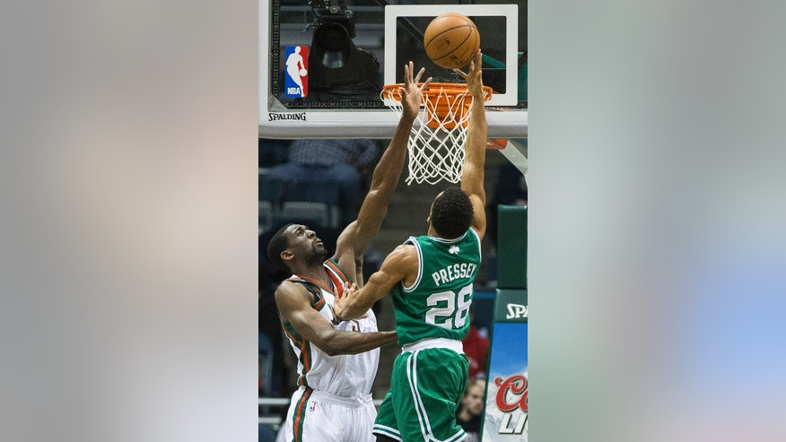 Milwaukee Bucks' Ekpe Udoh attempts to block the shot of Boston Celtics' Phil Pressey during the second half of an NBA basketball game, Monday, Feb. 10, 2014, in Milwaukee. (AP Photo/Tom Lynn)