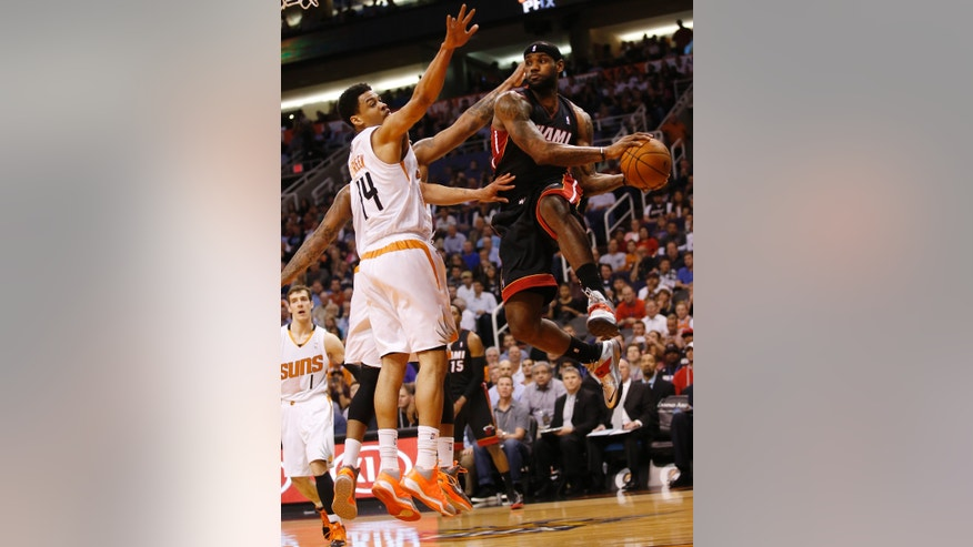 Miami Heat forward LeBron James passes the ball off while defended by Phoenix Suns guard Gerald Green during the first half of an NBA basketball game Tuesday, Feb. 11, 2014, in Phoenix. (AP Photo/The Arizona Republic, Michael Chow) MAGS OUT  NO SALES  MESA OUT  MARICOPA COUNTY OUT