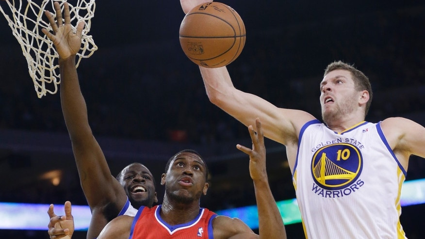 Golden State Warriors' David Lee (10) grabs a rebound next to Philadelphia 76ers' Thaddeus Young (21) and teammate Draymond Green, left, during the first half of an NBA basketball game, Monday, Feb. 10, 2014, in Oakland, Calif. (AP Photo/Marcio Jose Sanchez)