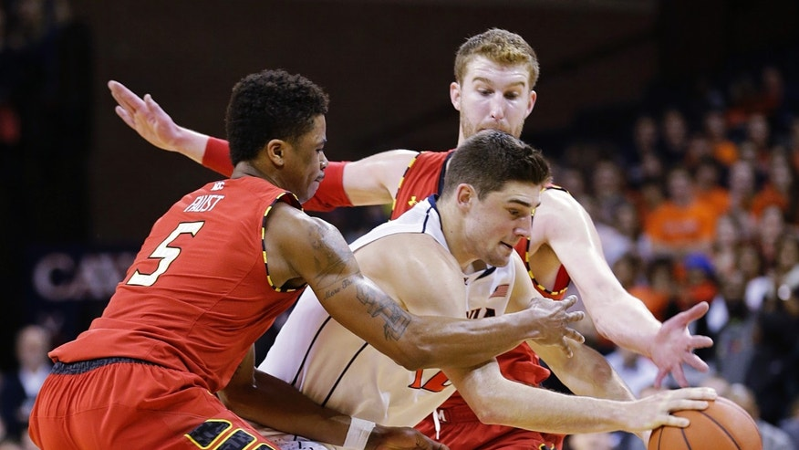 Maryland forward Evan Smotrycz, back, and teammate guard Nick Faust (5)  pressure Virginia guard Joe Harris during the second half of an NCAA college basketball game in Charlottesville, Va., Monday, Feb. 10, 2014. Virginia won the game 61-53. (AP Photo/Steve Helber)