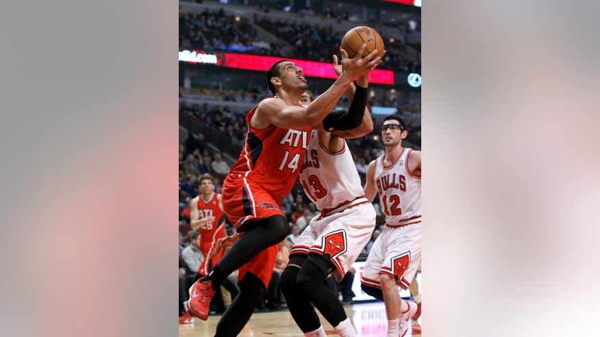 Atlanta Hawks forward Gustavo Ayon (14) drives past Chicago Bulls center Joakim Noah (13) during the first half of an NBA basketball game Tuesday, Feb. 11, 2014, in Chicago. (AP Photo/Charles Rex Arbogast)