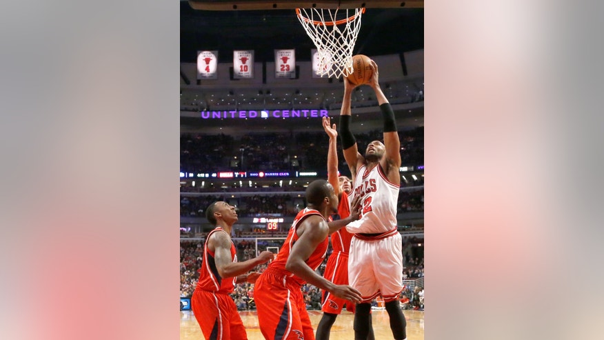 Chicago Bulls forward Taj Gibson (22) shoots over Atlanta Hawks' Jeff Teague, left, Elton Brand, center, and Gustavo Ayon during the first half of an NBA basketball game Tuesday, Feb. 11, 2014, in Chicago. (AP Photo/Charles Rex Arbogast)