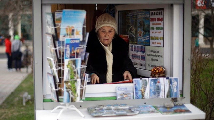 Feb. 10, 2014: In this photo, 74-year-old Sochi native Dina Kobolenko waits for tourists in her kiosk selling maps, books and postcards outside the central train station in Sochi, Russia. Vladimir Putin isnt the only one who has a lot riding on the success of the Sochi Olympics. Local businesses and residents have a lot to gain if these Olympics fulfill Putins pledge to turn Sochi and its environs from a summer playground for well-off Russians into a year-round international resort for everyone.