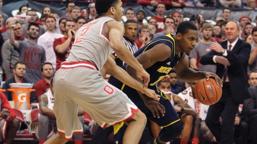 Michigan's Glenn Robinson, right, dribbles around Ohio State's Marc Loving during the first half of an NCAA college basketball game, Tuesday, Feb. 11, 2014, in Columbus, Ohio. (AP Photo/Jay LaPrete)