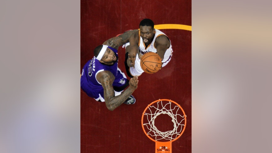 Cleveland Cavaliers' Luol Deng, from Sudan, right, shoots over Sacramento Kings' DeMarcus Cousins during the first half of an NBA basketball game Tuesday, Feb. 11, 2014, in Cleveland. (AP Photo/Mark Duncan)