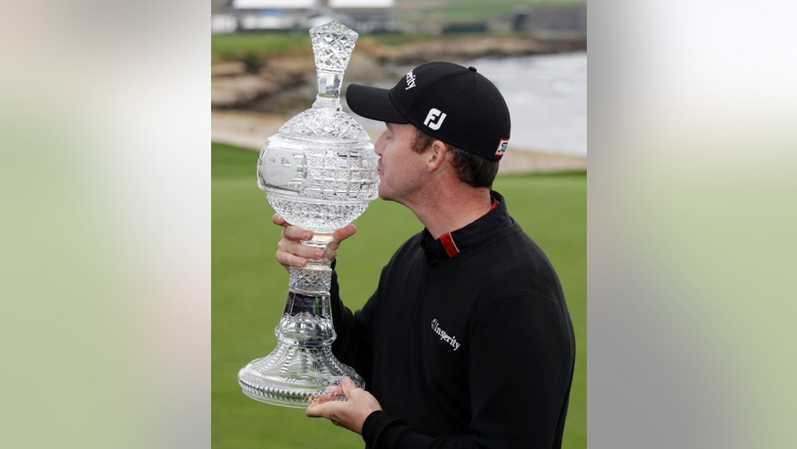 Jimmy Walker kisses his trophy on the 18th green of the Pebble Beach Golf Links after winning the AT&T Pebble Beach Pro-Am golf tournament Sunday, Feb. 9, 2014, in Pebble Beach, Calif. Walker shot a 2-over-par 74 to finish at total 11-under-par. (AP Photo/Eric Risberg)