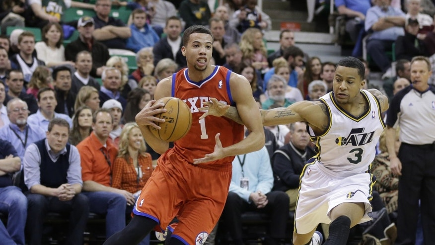 Utah Jazz's Trey Burke (3) reaches for the ball as Philadelphia 76ers' Michael Carter-Williams (1) drives in the second quarter of an NBA basketball game on Wednesday, Feb. 12, 2014, in Salt Lake City. (AP Photo/Rick Bowmer)