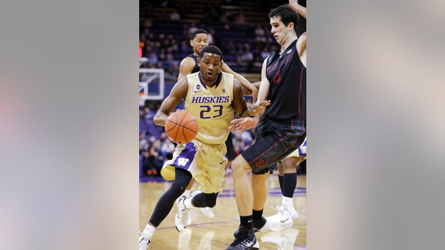 Washington's C.J. Wilcox (23) tries to drive past Stanford's Stefan Nastic in the first half of an NCAA college basketball game Wednesday, Feb. 12, 2014, in Seattle. (AP Photo/Elaine Thompson)