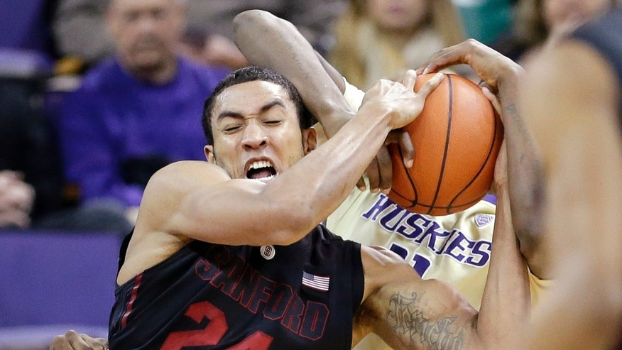 Stanford's Josh Huestis (24) ties up the ball with a Washington player in the first half of an NCAA college basketball game Wednesday, Feb. 12, 2014, in Seattle. (AP Photo/Elaine Thompson)