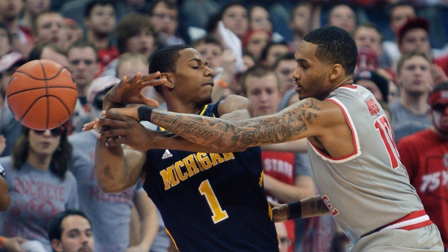 Ohio State's LaQuinton Ross, right, knocks the ball away from Michigan's Glenn Robinson during the second half of an NCAA college basketball game Tuesday, Feb. 11, 2014, in Columbus, Ohio. Michigan defeated Ohio State 70-60. (AP Photo/Jay LaPrete)