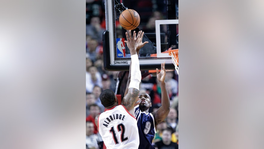 Oklahoma City Thunder center Serge Ibaka, right, tries to block a shot by Portland Trail Blazers forward LaMarcus Aldridge during the first half of an NBA basketball game in Portland, Ore., Tuesday, Feb. 11, 2014. (AP Photo/Don Ryan)