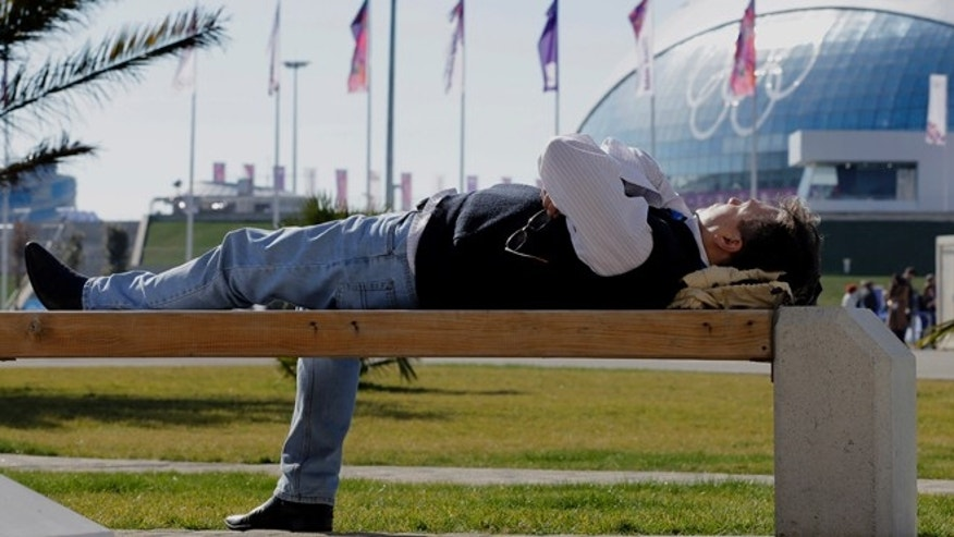 Feb. 12, 2014: A man lies on a bench in the warm sunlight inside the Olympic Park at the 2014 Winter Olympics in Sochi, Russia.