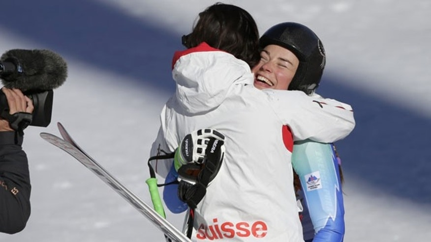 February 12, 2014: Slovenia's Tina Maze, right, and Switzerland's Dominique Gisin embrace after finishing the women's downhill at the Winter Olympics. (AP Photo/Gero Breloer)