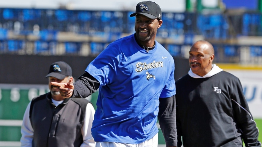 Retired NBA All-Star Tracy McGrady points to the catcher after throwing a pitch into the dirt during a workout at the Sugar Land Skeeters baseball stadium Wednesday, Feb. 12, 2014, in Sugar Land, Texas as manager Gary Gaetti, left, and former major league pitcher Scipio Spinks stand near. McGrady hopes to tryout as a pitcher for the independent Atlantic League Skeeters. (AP Photo/Pat Sullivan)