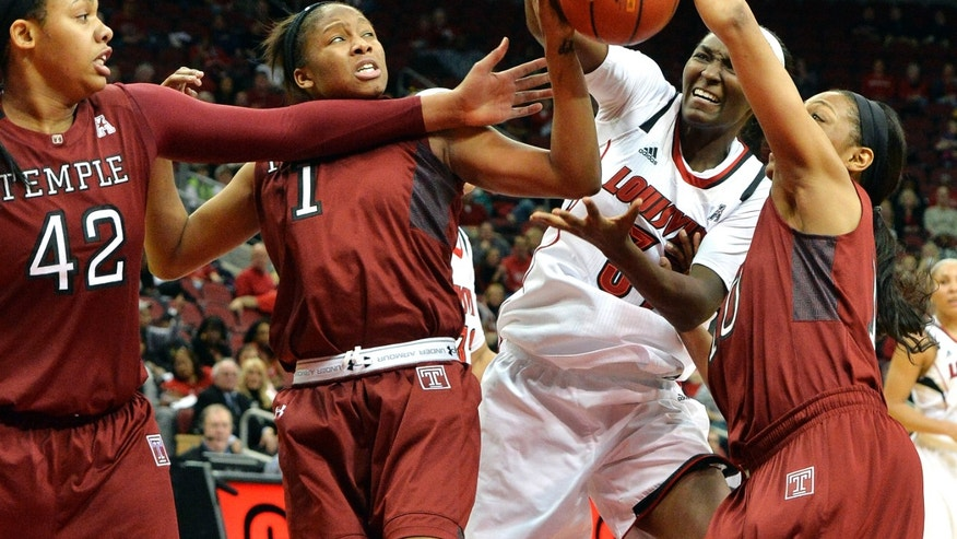 Louisville's Asia Taylor, third from left, battles Temple's Taylor Robinson, left, Erica Coville, second from left, and Shi-Heria Shipp for a rebound during the first half of an NCAA college basketball game Wednesday, Feb. 12, 2014, in Louisville, Ky. (AP Photo/Timothy D. Easley)