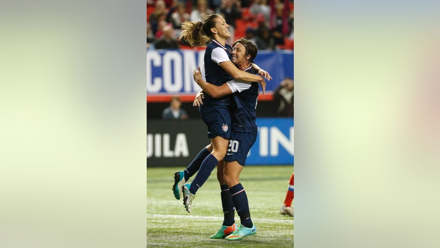 United States'Lauren Holiday (12) celebrates with Abby Wambach (20) after scoring during the second half of a an exhibition soccer match against Russia on Thursday, Feb. 13, 2014, in Atlanta. The United States won 8-0. (AP Photo/John Bazemore)