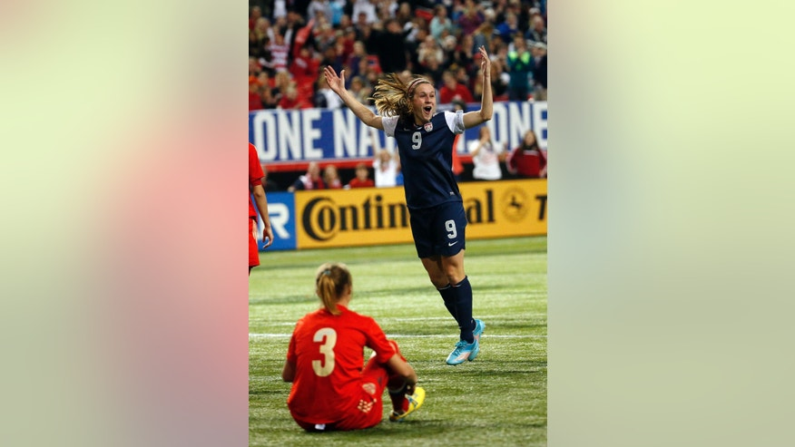 United State's Heather O'Reilly (9) celebrates in front of Russia's Valentina Orlova (3) after scoring a goal in the second half of an exhibition  soccer match Thursday, Feb. 13, 2014, in Atlanta. United States won 8-0. (AP Photo/John Bazemore)