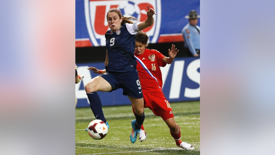 United State's Heather O'Reilly (9) gets past Russia's Elena Kostareva (16) as she scores a goal in the second half of a soccer match Thursday, Feb. 13, 2014, in Atlanta. United States won 8-0. (AP Photo/John Bazemore)