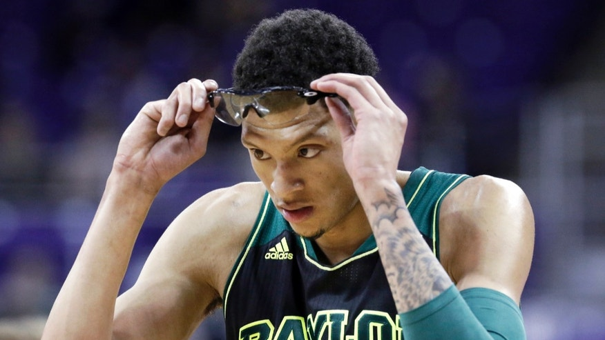 FILE - In this Feb. 12, 2014, file photo, Baylor center Isaiah Austin (21) adjusts his glasses during the first half of an NCAA college basketball game against TCU in Fort Worth, Texas. Austin came to the realization as a teenager that he'd never again see out of his right eye. Multiple operations couldn't save his vision after a previous injury was aggravated doing a routine dunk before a middle school game. (AP Photo/LM Otero, File)
