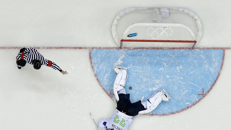 A referee signals a goal as Slovenia goaltender Robert Kristan lays on the ice after Russia defenseman Anton Belov scored in the third period of a men's ice hockey game at the 2014 Winter Olympics, Thursday, Feb. 13, 2014, in Sochi, Russia. Russia won 5-2.(AP Photo/Mark Humphrey )