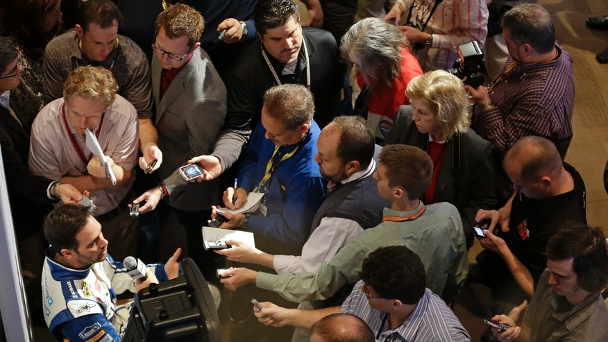 Driver Jimmie Johnson, left, is surrounded by reporters during an interview at  NASCAR auto racing media day at Daytona International Speedway in Daytona Beach, Fla., Thursday, Feb. 13, 2014. (AP Photo/John Raoux)