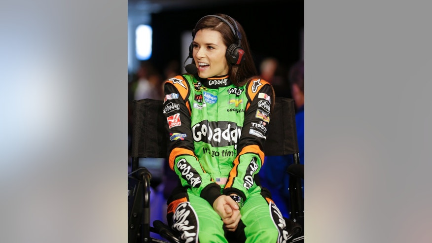 Driver Danica Patrick laughs at a question during an interview at NASCAR auto racing media day at Daytona International Speedway in Daytona Beach, Fla., Thursday, Feb. 13, 2014. (AP Photo/John Raoux)
