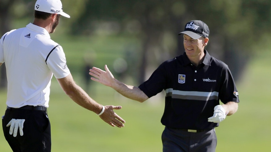 CORRECTS TO BIRDIE, NOT EAGLE - Jim Furyk, right, is congratulated by Dustin Johnson after Furyk made birdie on the second green in the first round of the Northern Trust Open golf tournament at Riviera Country Club in the Pacific Palisades area of Los Angeles Thursday, Feb. 13, 2014.  (AP Photo/Reed Saxon)