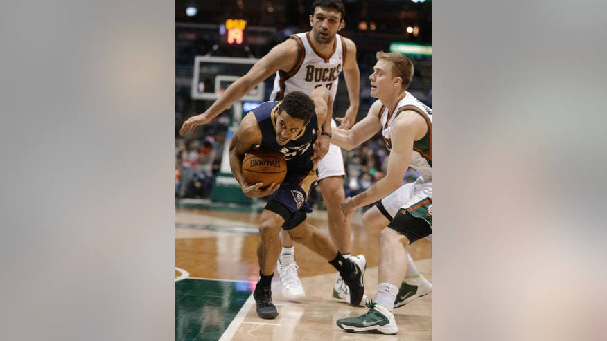 New Orleans Pelicans' Brian Roberts, left, drives against Milwaukee Bucks' Nate Wolters, right, during the second half of an NBA basketball game Wednesday, Feb. 12, 2014, in Milwaukee. (AP Photo/Jeffrey Phelps)
