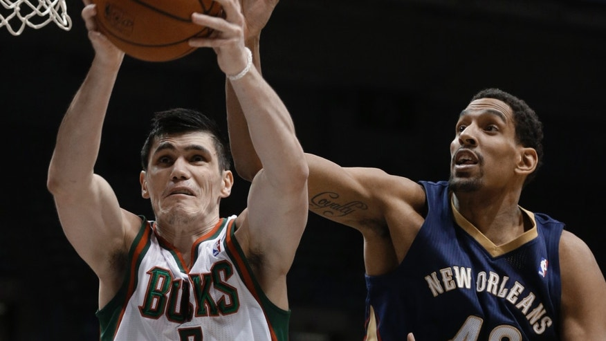 Milwaukee Bucks' Ersan Ilyasova (7) and New Orleans Pelicans' Alexis Ajinca (42) reach for a rebound during the second half of an NBA basketball game Wednesday, Feb. 12, 2014, in Milwaukee. (AP Photo/Jeffrey Phelps)