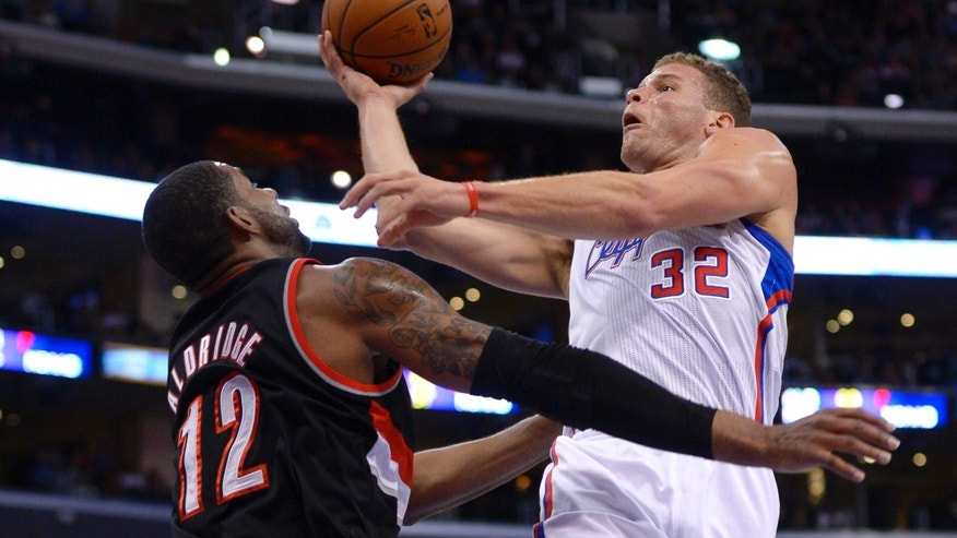 Los Angeles Clippers forward Blake Griffin, right, puts up a shot as Portland Trail Blazers forward LaMarcus Aldridge defends during the first half of an NBA basketball game, Wednesday, Feb. 12, 2014, in Los Angeles. (AP Photo/Mark J. Terrill)