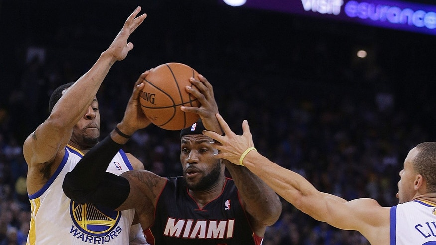 Miami Heat's LeBron James, center, drives the ball between Golden State Warriors' Andre Iguodala, left, and Stephen Curry (30) during the first half of an NBA basketball game Wednesday, Feb. 12, 2014, in Oakland, Calif. (AP Photo/Ben Margot)